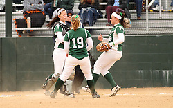 30 March 2013:  Katie Crane pulls in a popped up ball in front of Chloe Montgomery and Emma Clark during an NCAA Division III women's softball game between the DePauw Tigers and the Illinois Wesleyan Titans in Bloomington IL<br />
