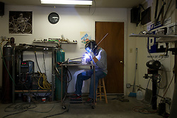 2010 FEB 12-Joe Depaemelaere, owner of Primus Mootry Bikes, works in his home shop to piece together a road frame.