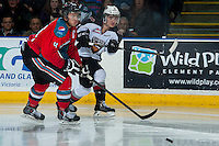 KELOWNA, CANADA - MARCH 15: Thomas Foster #16 of the Vancouver Giants takes a shot as Madison Bowey #4 of the Kelowna Rockets checks him during second period on March 15, 2014 at Prospera Place in Kelowna, British Columbia, Canada.   (Photo by Marissa Baecker/Getty Images)  *** Local Caption *** Madison Bowey; Thomas Foster;
