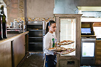 "NAPLES, ITALY - 8 DECEMBER 2017: A waitress carries pizzas here at Pizzeria Gino Sorbillo in Naples, Italy, on December 8th 2017.<br /> <br /> On Thursday December 7th 2017, UNESCO added the art of Neapolitan ""Pizzaiuolo"" to its list of Intangible Cultural Heritage of Humanity.<br /> <br /> The art of the Neapolitan 'Pizzaiuolo' is a culinary practice comprising four different phases relating to the preparation of the dough and its baking in a wood-fired oven, involving a rotatory movement by the baker. The element originates in Naples, the capital of the Campania Region, where about 3,000 Pizzaiuoli now live and perform. Pizzaiuoli are a living link for the communities concerned. There are three primary categories of bearers – the Master Pizzaiuolo, the Pizzaiuolo and the baker – as well as the families in Naples who reproduce the art in their own homes. The element fosters social gatherings and intergenerational exchange, and assumes a character of the spectacular, with the Pizzaiuolo at the centre of their 'bottega' sharing their art.<br /> <br /> In Naples, pizza makers celebrated the victory by giving away free pizzas."