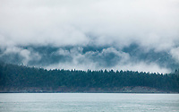 Low clouds over the San Juan Island as seen from aboard a Washington State Ferry on the way from Anacortes to Orcas Island, Washington, USA.