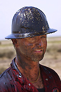 "Mike of Boots and Coots after getting covered with oil while running a backhoe. The gusher was capped two hours later using a ""stinger,"" a tapered pipe on the end of a long steel boom controlled by a bulldozer. Drilling mud, under high pressure, is pumped through the stinger into the well, stopping the flow of oil and gas. The Rumaila field is one of Iraq's biggest oil fields with five billion barrels in reserve. Rumaila is also spelled Rumeilah."