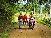 21 JUNE 2016 - DON KHONE, CHAMPASAK, LAOS: Women riding in a tuk-tuk, or three wheeled taxi, on Don Khone. Three years ago there were no tuk-tuks on Don Khone, now there are more than 50. Most serve the tourists but more and more local people are using them. Don Khone Island, one of the larger islands in the 4,000 Islands chain on the Mekong River in southern Laos. The island has become a backpacker hot spot, there are lots of guest houses and small restaurants on the north end of the island.       PHOTO BY JACK KURTZ