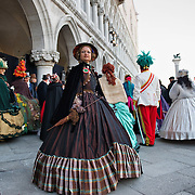 "VENICE, ITALY - FEBRUARY 19:  Members of the association ""Amici del Carnevale di Venezia"" wearing 19th century costumes pose in St Mark Square on February 19, 2011 in Venice, Italy. The fountain pouring wine features today during the Gran brindisi a Venezia or Grand Toast in Venice, the opening ceremony of this year Carnival ."