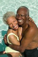 Senior Couple hugging in swimming pool elevated view portrait.