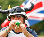 Ian Ashmead shoots his hi tech laser sighted pea shooter during the World Peashooting Championships held at Witcham, Cambridgeshire, UK on 13th July 2013. Run in conjunction with the village fair, the Championships have been held in Witcham since 1971 when they were started by a Mr Tyson, the village schoolmaster, in order to raise funds for the village hall.Competitors come from as far afield as the USA and New Zealand to attempt to win the event. The latest technology is often used, including laser sights and titanium and carbon fibre peashooters. All peashooters must conform to strict length rules, not exceeding 12 inches, and have to hit a target 12 feet away. Shooting 5 peas at a plasticine target attached to a hay bale, the highest scorers move through the initial rounds to a knockout competition, followed by a sudden death 10-pea shootout.