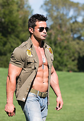 man in an open military style shirt and sunglasses walking outdoors