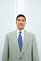 A portrait of a mid 30's Asian business man standing in front of a narrow vertical window in a white room..20050916_MR_A.20050916_PR_A