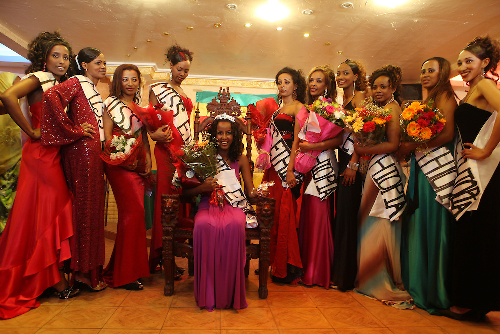 The winner of the first ever Miss Ethiopia beauty pageant in Lebanon sits posing for a photograph surrounded by the other 10 women who took part in the competition.