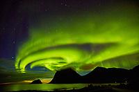 The Northern Lights (Aurora borealis) illuminate the sky over Haukland beach in the Lofoten Islands of Norway