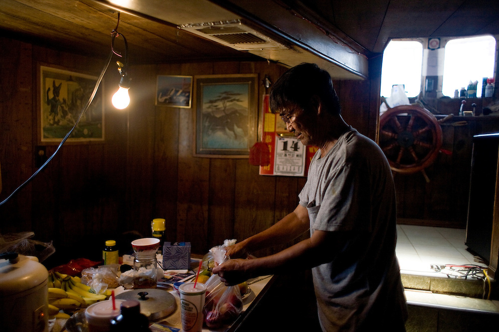 Roi-van Nguyen, 63, packs food on the H&R shrimp boat in Grand Isle, LA on June 24, 2010 where a fishing ban has been put in place due to the B.P. oil spill. The H&R crew will head west in hopes to find open fishing waters after waiting two months for B.P. to hire their boat.