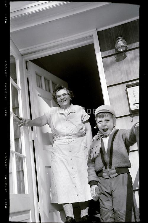 grandmother with grandchild in door opening USA 1950s