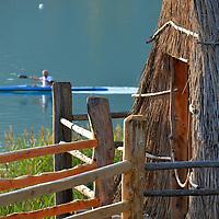 Palafitta dello sciamano realizzata in legno e canne palustri; sullo sfondo un signore pratica canottaggio sulle acque del Lago di Ledro