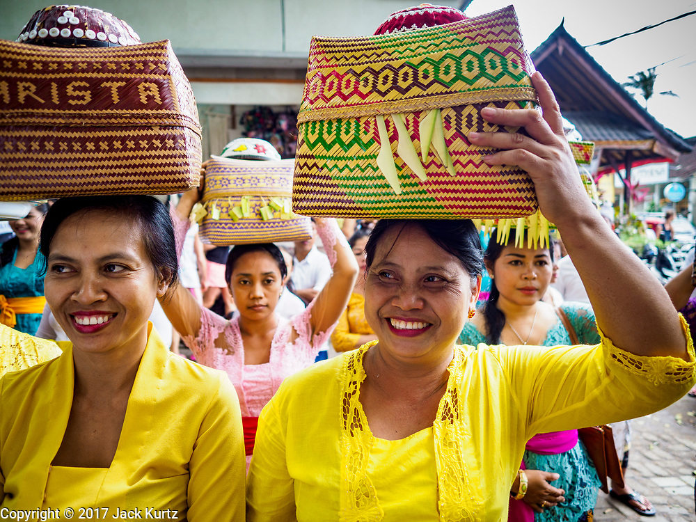 """02 AUGUST 2017 - UBUD, BALI, INDONESIA: Women wait to go into the temple during the """"Merchants' Day"""" ceremony at the Pura (Temple) Melanting Pasar Ubud, the small Hindu temple in the Ubud market. It's a day that merchants throughout Ubud come to the temple to make offerings and pray for prosperity.    PHOTO BY JACK KURTZ"""