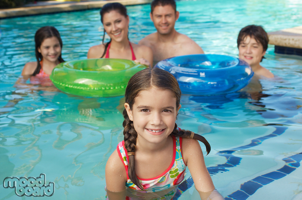 Family with two girls and boy with inflatable rafts, in swimming pool,  portrait