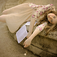 Young girl with pale skin and blond hair dressed in a pale pink dress lying next to a fountain and holding a pocket watch