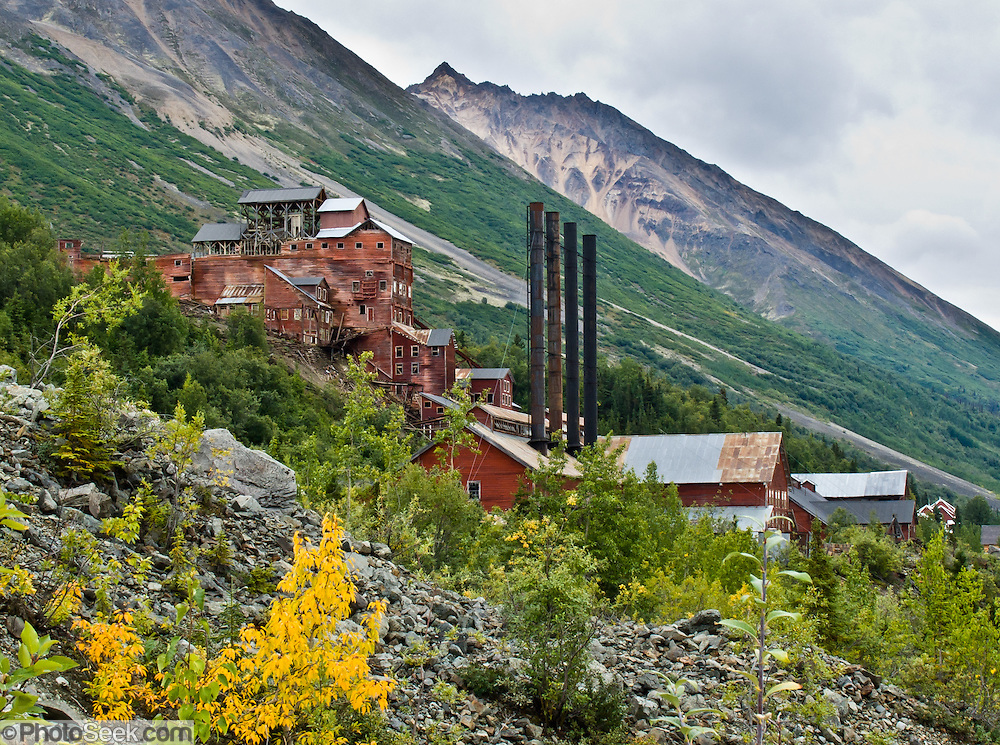 "14-story tall Kennecott Concentration Mill processed copper ore 1911-1938. Kennecott Mines National Historic Landmark and nearby McCarthy nestle under Bonanza Ridge in the Wrangell Mountains within Wrangell-St. Elias National Park and Preserve, Alaska, USA. Old mine buildings, artifacts, and colorful history attract summer visitors. Remote McCarthy is connected to Chitina via the McCarthy Road spur of the Edgerton Highway. At the east end of McCarthy Road, visitors must park their vehicle and walk across the footbridge to McCarthy. From McCarthy, a privately-operated shuttle takes visitors 5 miles to Kennecott. After copper was discovered between the Kennicott Glacier and McCarthy Creek in 1900, the Kennecott town, mines, and Kennecott Mining Company were created and named after the adjacent glacier. Kennicott Glacier and River had previously been named after Robert Kennicott, a naturalist who explored in Alaska in the mid-1800s. The corporation and town stuck with a mistaken spelling of ""Kennecott"" with an e (instead of ""Kennicott"" with an i). Partly because alcoholic beverages and prostitution were forbidden in the company town of Kennecott, the neighboring town of McCarthy grew quickly to provide a bar, brothel, gymnasium, hospital, and school. The Copper River and Northwestern Railway reached McCarthy in 1911 to haul over 200 million dollars worth of ore 196 miles to the port of Cordova on Prince William Sound. By 1938, the worlds richest concentration of copper ore was mostly gone, the town was mostly abandoned, and railroad service ended. Not until the 1970s did the area began to draw young people for adventure and the big money of the Trans Alaska Pipeline project. Declaration of Wrangell-St. Elias National Park in 1980 drew adventurous tourists who helped revive McCarthy with demand for needed services. Wrangell-St. Elias National Park and Preserve (the largest National Park in the USA) is honored by UNESCO as part of a World Heritage Site."