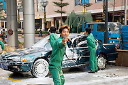 Shenzhen city centre, Guangdong Province, China. Young laughing man pointing water hose at street car wash