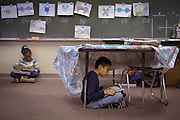 Marietta, GA January 14, 2006<br /> <br /> Omosaze  reading program<br /> <br /> Miquel Macias finds a quiet spot under a desk to read.  Some photos have Kelsea Duncan in background.