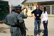 "Pilot, Danielle Aitchison, and her partner, Captain Chris Hood, pose for a photo for Afghan security soldiers at Kabul International Airport.  Danielle flies in Afghanistan for The United Nations Humanitarian Air Service (UNHAS).   ...When asked about flying in a war zone, she says,  ""I'm just a normal average female.  My job is maybe a little different to some, but I have the same feminine side as other women.  I don't have any trouble going back to New Zealand relating to people.  I'm just a regular chick.""."