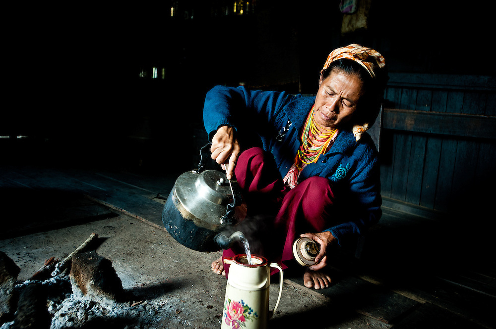 A Naga woman makes tea for her family.