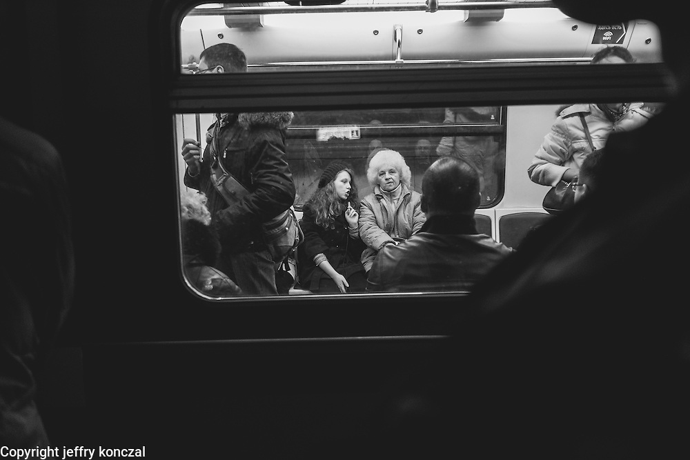 An older women and girl talk while on the Moscow Metro.