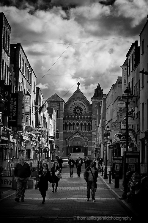 People walking on South Ann Street, Just off Grafton Street in Dublin, with a Moody sky overhead.