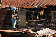 A woman walks past destroyed houses in the village of Kpoto, Benin on Tuesday October 26, 2010.  Waters have receded in Kpoto, but most of the village was literally flattened by floods that have hit Benin over the past few weeks..