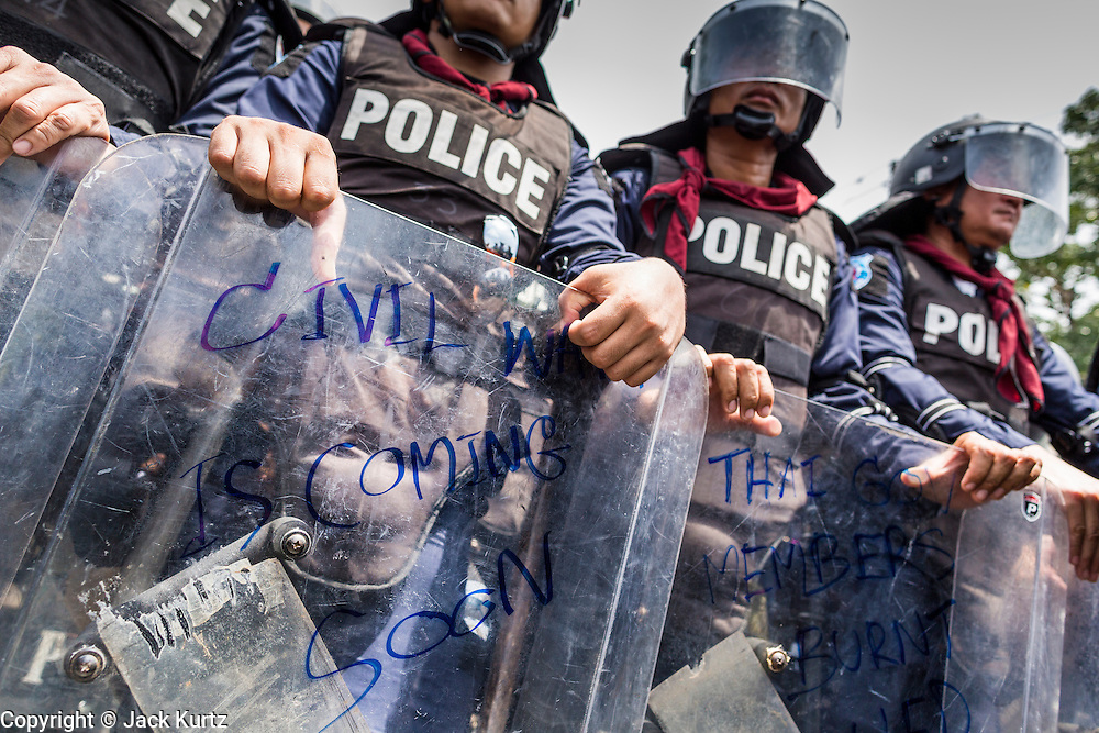 "07 AUGUST 2013 - BANGKOK, THAILAND:  A Thai riot policemen leans on his shield, which a protester defaced by writing ""civil war is coming soon"" on during an anti-government protest near the parliament building in Bangkok. About 2,500 protestors opposed to an amnesty bill proposed by Thailand's ruling party marched towards the Thai parliament in the morning. The amnesty could allow exiled fugitive former Prime Minister Thaksin Shinawatra to return to Thailand. Thaksin's supporters are in favor of the bill but Thai Yellow Shirts and government opponents are against the bill. Thai police deployed about more than 10,000 riot police and closed roads around the parliament. Although protest leaders called off the protest rather than confront police, a few people were arrested for assaulting police when they tried to break through police lines. Several police officers left the scene under medical care after they collapsed in the heat.     PHOTO BY JACK KURTZ"