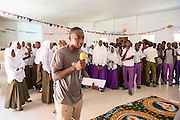 VSO ICS volunteer Nasir Bakari welcomes the children of the community for the first part of the VSO ICS Community Action Day CAD in Y2K Hall Lindi, Lindi region. Tanzania.