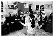 Two young girls from a local orphanage are dancing in front of the local women and workers from the orphanage. Qalqilia, Palestine, 2007
