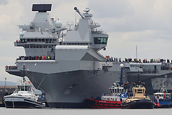 A police boat on the Firth of Forth as HMS Queen Elizabeth, one of two new aircraft carriers for the Royal Navy, begins to leave the Rosyth dockyard near Edinburgh to begin her sea worthiness trials.