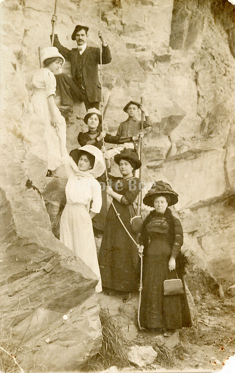 an early tourist photo with people posing as rock climbers