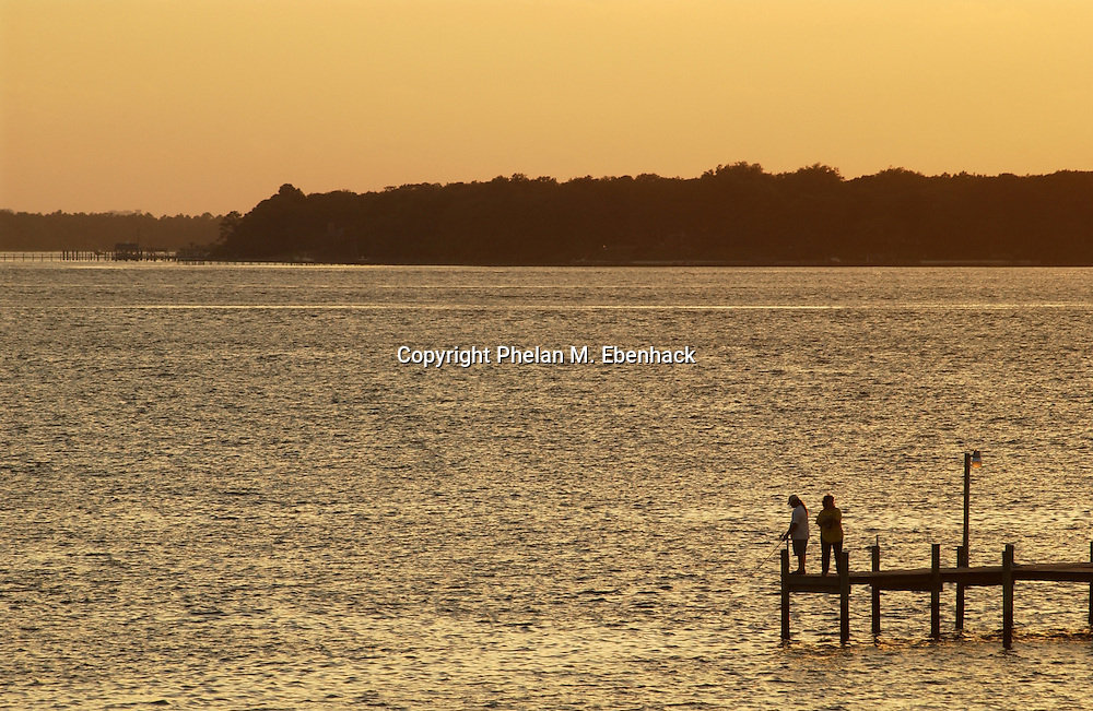 Two people fish from a pier in the waters of St. Andrews Bay in Panama City, Florida.