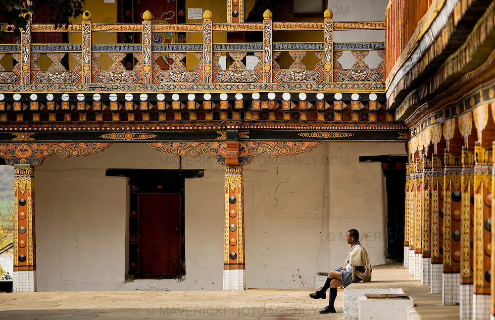 A man seated on the steps of Punakha dzong, Punakha..Commonly described as the last Himalayan Shangrila, Bhutan is a country of unique serenity, harmony, and beauty. Nestled between India, China, and Tibet, this independent country whose name translates as 'the Land of the Thunder Dragon' has for the past 300 years  proactively followed a policy of isolation and cultural protection. Travel in and out of the country is strictly regulated, and the impact of outside influences on the local culture is carefully monitored. Spirituality is an important aspect of Bhutanese culture, with Buddhism being interlinked with everyday life. Gross National Happiness (GNH), as opposed to GNP/GDP, forms the cornerstone of its development strategy which focuses on a holistic development strategy that complements its cultural and Buddhist spiritual values.