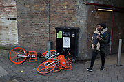 A potential trip hazard for a mother carrying her infant with a pile of three abandoned dockless Mobikes left in the street near Waterloo Station, on 4th March 2019, in London England.