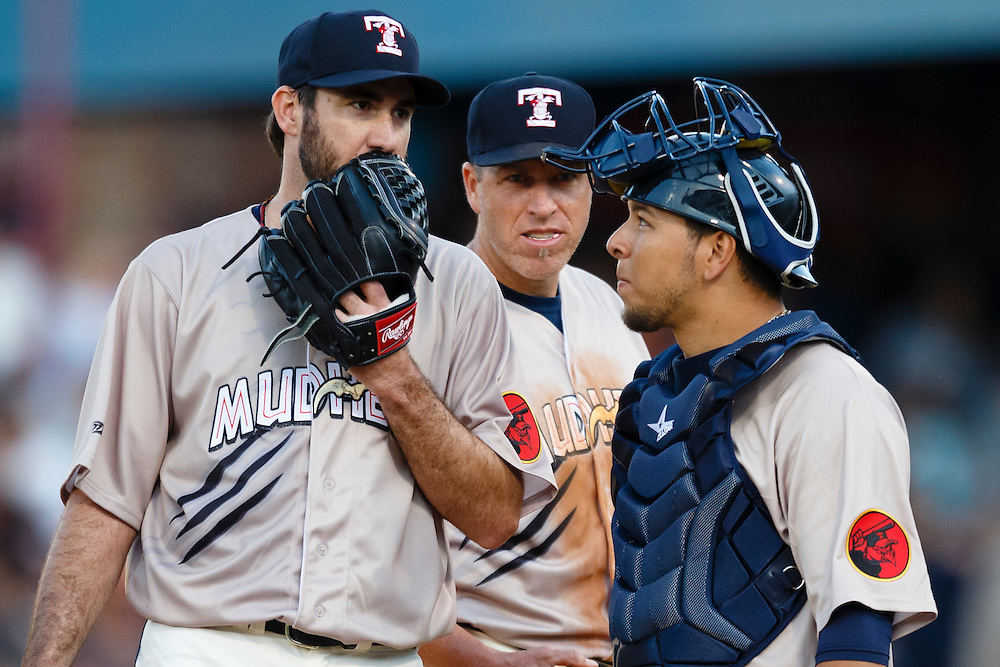 Detroit Tigers pitcher Justin Verlander, playing for the Toledo Mud Hens in a rehab start, talks to catcher Miguel Gonzalez, right, and first baseman Mike Hessman, center, in the sixth inning during a Triple-A baseball game against the Columbus Clippers in Toledo, Ohio, Saturday, June 6, 2015. (AP Photo/Rick Osentoski)