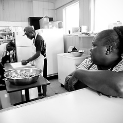 Kyle Green | The Roanoke Times<br /> 5/31/2012 Emma Davis (right) waits for Clifford Folkes (left) and Phil Folkes (middle) to finish preparing curry chicken at Cliff&rsquo;s Jammerican Restaurant located on Orange Avenue in NW Roanoke, Virginia. Cliff&rsquo;s Jammerican Restaurant is now one of two or three Jamaican restaurants in Roanoke. Cliff&rsquo;s is owned by Clifford Folkes, who moved to the U.S. from his native Jamaica about 30 years ago. But Cliff&rsquo;s has only been open for about 8 months.