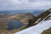 Red Tarn lake high up on the eastern flank of Helvellyn Mountain, English Lake District, Cumbria, UK.  Red Tarn is a glacial lake formed with the glacier that carved our the eastern side of the mountain melted. It is the habitat of the rare and endangered Schelly fish. It is a sunny day, but there is snow on the summit of the mountain.  (photo by Andrew Aitchison / In pictures via Getty Images)