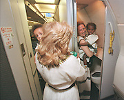 8/8/01 -- (PHOTO BY MIKE FENDER) w/ story, slug: AFRICA, file: 62040 // Six babies on a 17 hour plane trip required several trips to change diapers on the Ethiopian airlines plane. Cheryl Carter-Shotts, left, carries Beza on her shoulder as she waits on escort Donna Cohen, right, with Tsehay, to exit the bathroom.