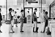 Nederland, Nijmegen, 15-10-1987Op het centraal station van Nijmegen staat een rij reizigers voor het loket om een kjaartje te kopen. Tussen hen ik een mededeling dat kaartjes uit de automaat goedkoper zijn.Foto: Flip Franssen/Hollandse Hoogte