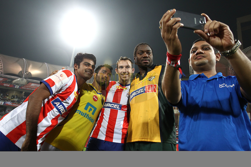 Mohammed Rafique of Atletico de Kolkata, Ishfaq Ahmed of Kerala Blasters FC, Atletico de Kolkata captain Jose Miguel Gonzalez Rey and Atletico de Kolkata goalkeeper Edel Apoula Edima Bete have a selfie with the Samsung Fan during the final of the Hero Indian Super League between Kerala Blasters FC and Atletico de Kolkata held at the D.Y. Patil Stadium, Navi Mumbai, India on the 2oth December 2014.<br /> <br /> Photo by:  Shaun Roy / ISL/ SPORTZPICS