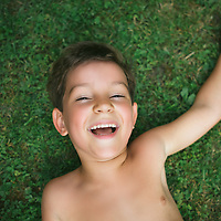 Portrait of a cute 5 year old boy lying on the grass with one arm raised behind his head