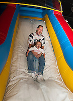 "Dan Perkins holds on tight to his daughter Bailey as they go down the slide during the first annual ""Jump a Thon"" at Jump 'n Joy to benefit the 2012 WLNH Children's Auction.  (Karen Bobotas/for the Laconia Daily Sun)"
