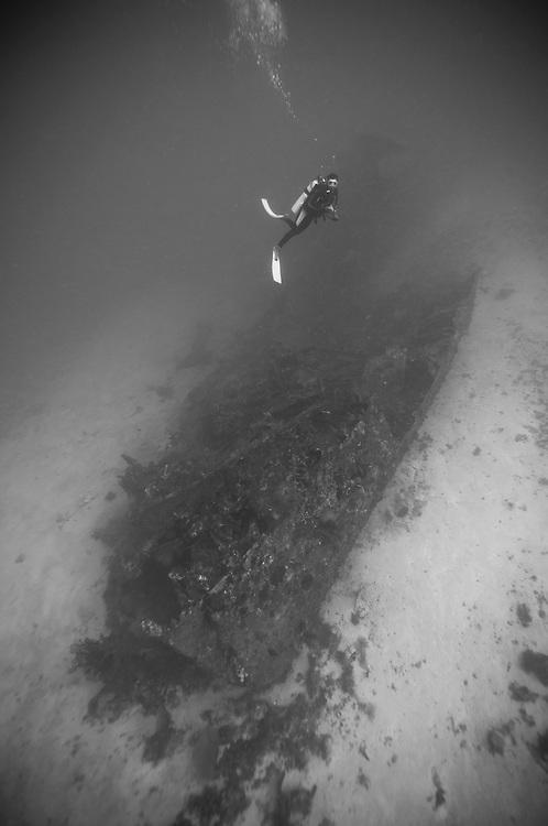 A diver descending to a deep, unidentified ship wreck near Manokwari, Wesp Papua, Indonesia.