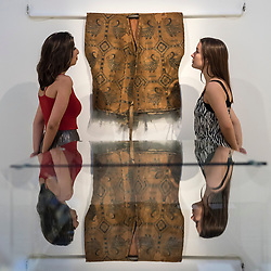 "© Licensed to London News Pictures. 20/04/2018. LONDON, UK. Staff members view ""An exceptional silk samite shirt with ducks"", Central Asia, Sogdiana, 7th-9th century (Est. GBP300-500k) at a preview of works in Sotheby's 20th Century Middle East, Orientalist and Islamic upcoming art sales in New Bond Street.  The works will be sold at auction in the last week of April.    Photo credit: Stephen Chung/LNP"