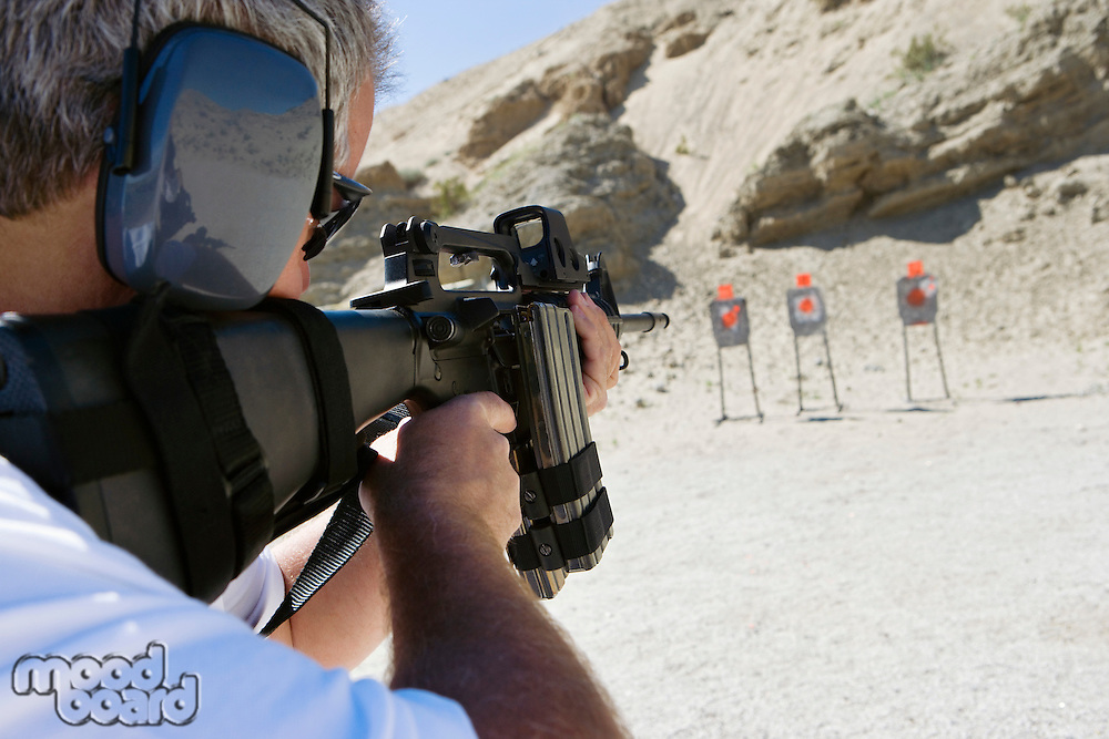 Man aiming machine gun at firing range