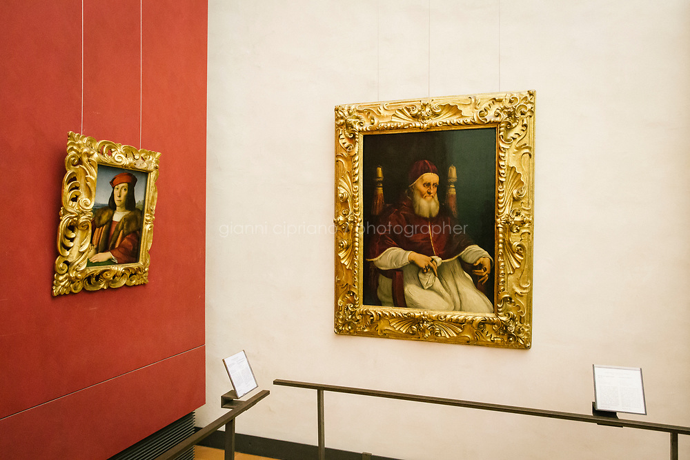FLORENCE, ITALY - 3 JUNE 2018: &quot;Portrait of a Young Man with an Apple&quot; (1504-1505 ca) and &quot;Portrait of Pope Julius II&quot; (1511-1512 ca) by Raphael are seen here at the Uffizi before being relocated at Palazzo Pitti, in Florence, Italy, on June 3rd 2018.<br /> <br /> As of Monday June 4th 2018, Room 41 or the &ldquo;Raphael and Michelangelo room&rdquo; of the Uffizi is part of the rearrangement of the museum's collection that has<br /> been defining Uffizi Director Eike Schmidt&rsquo;s grander vision for the Florentine museum.<br /> Next month, the museum&rsquo;s Leonardo three paintings will be installed in a<br /> nearby room. Together, these artists capture &ldquo;a magic moment in the<br /> first decade of the 16th century when Florence was the cultural and<br /> artistic center of the world,&rdquo; Mr. Schmidt said. Room 41 hosts, among other paintings, the dual portraits of Agnolo Doni and his wife Maddalena Strozzi painted by Raphael round 1504-1505, and the &ldquo;Holy Family&rdquo;, that Michelangelo painted for the Doni couple a year later, known as the<br /> Doni Tondo.