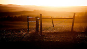 The sun sets over a fence in the Sandhills of Nebraska.