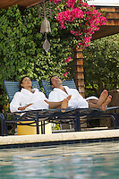 Couple in bathrobes relaxing by swimming pool